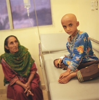 An image of a child without any hair sitting on a hospital bed with the mother looking on