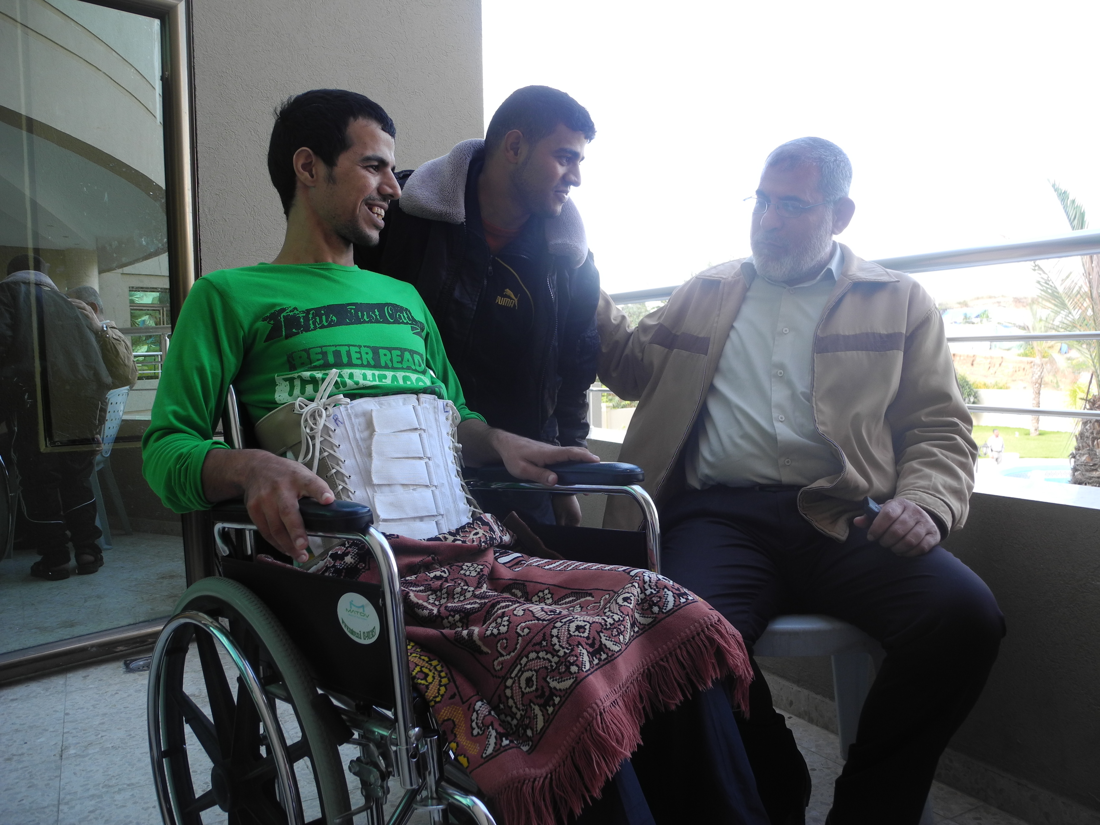 Abdelaziz, his brother (left), and Ali Abu Riala, the head of nursing department at Al-Wafa hospital (right).