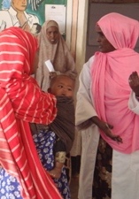 A woman carrying a child consults a medical worker at a health facility