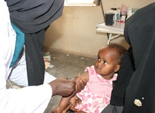 A child receives a measles jab from a vaccinator