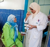 A health worker tells a patient how to take her TB treatment