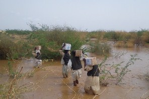 WHO staff and volunteers carrying boxes of medicines and supplies while they cross flooded areas to reach a health facility in Aroma locality, Kassala, East Sudan