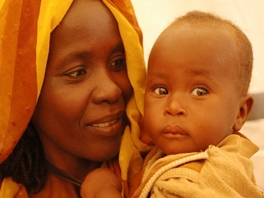 A Sudanese mother smiling as she holds her healthy baby