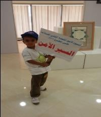 A young Sudanese boy holds up a banner promoting Road Safety Week