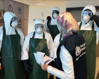 A trainer gives instructions to health workers wearing protective masks, goggles, gloves, hoods and coveralls