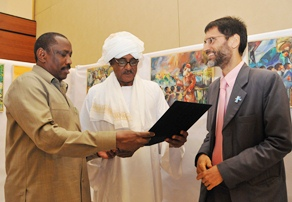 A photo of Sudan's Minister of Health and the WHO Representative together with one of the elderly artists whose works were featured at a painting exhibition to celebrate World Health Day.