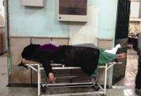 A woman lies motionless on a gurney in a corridor of a health facility