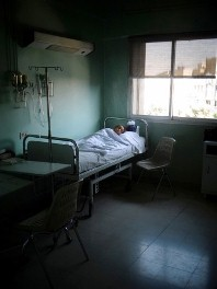 A child with polio lies in a hospital bed