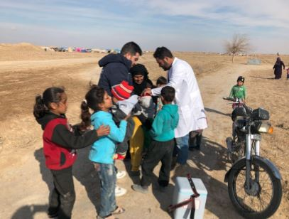 Vaccinators outside an informal tented settlement in Deir Ez-Zor administering polio vaccine to children, as part of the campaign. Photo: WHO
