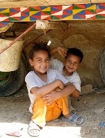 Two healthy Egyptian children smiling at the camera