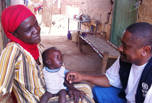 WHO staff speaking to mother and child in South Kordofan