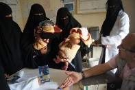 Women holding babies queue at a registration table where a health worker sits