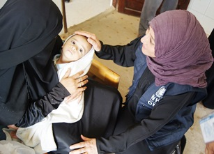 A mother holds her baby supported by WHO staff member