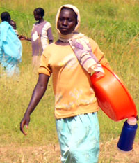 A young girl carrying a plastic bowl and a flask out of the fields